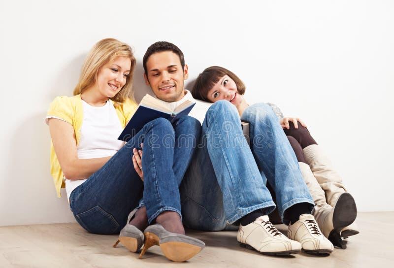 Drie vrienden met boeken stock afbeelding