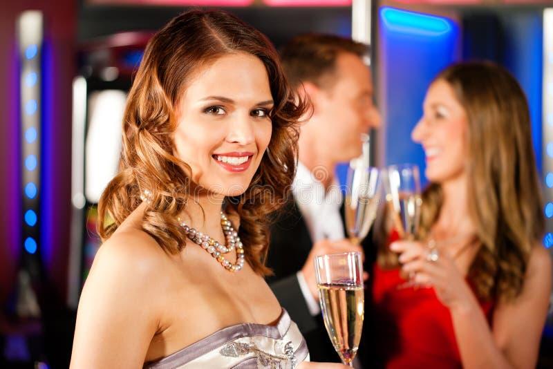 Drie vrienden met champagner in een staaf royalty-vrije stock afbeelding