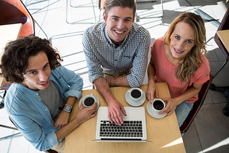 Drie vrienden met koffiekoppen die laptop in koffiewinkel met behulp van royalty-vrije stock fotografie