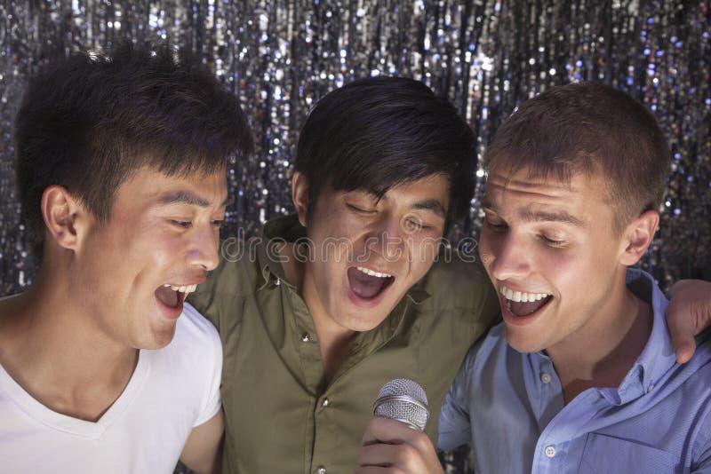 Drie vrienden met wapen rond elkaar die een microfoon houden en samen bij karaoke zingen stock afbeeldingen