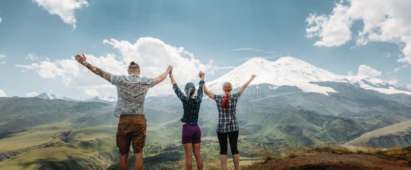 Drie vrienden sloten zich aan bij handen en hieven hun handen op omhoog, genietend van de mening van de bergen in de zomer Gelukk stock fotografie
