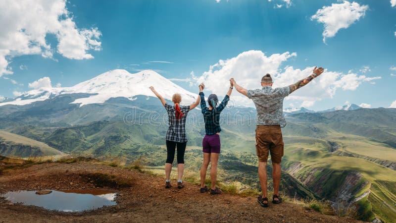 Drie vrienden sloten zich aan bij handen en hieven hun handen op omhoog, genietend van de mening van de bergen in de zomer De zom stock foto's