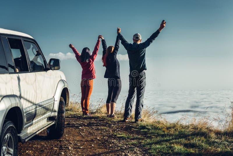 Drie vrienden sloten zich aan bij handen en hieven hun handen op omhoog, genietend van de mening van Openlucht Het Concept van de royalty-vrije stock foto