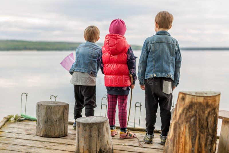 Drie vrienden spelen visserij op houten pijler dichtbij vijver Twee peuterjongens en één meisje bij rivierbank Kinderen die pret  royalty-vrije stock afbeelding