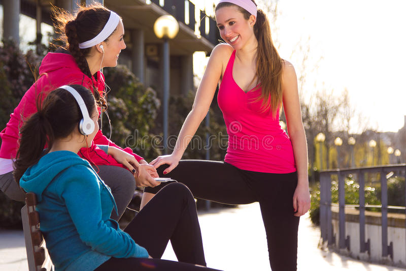 Drie vriendenwhit sportkleding die na oefening spreken stock foto's