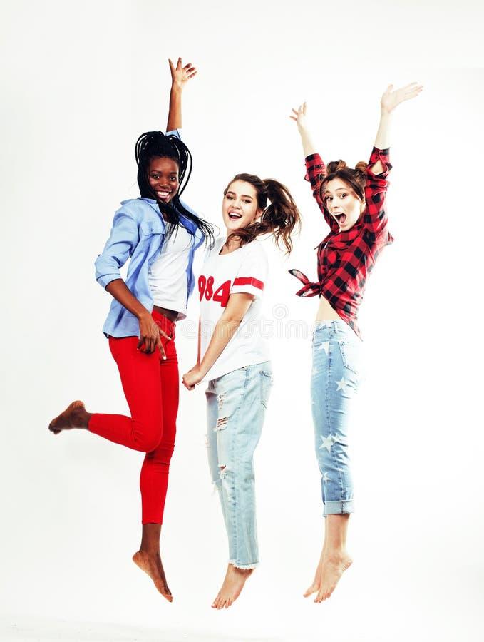Drie vrij jonge diverse vrienden die van de natiestiener het gelukkige glimlachen op witte achtergrond, levensstijlmensen springe royalty-vrije stock foto's