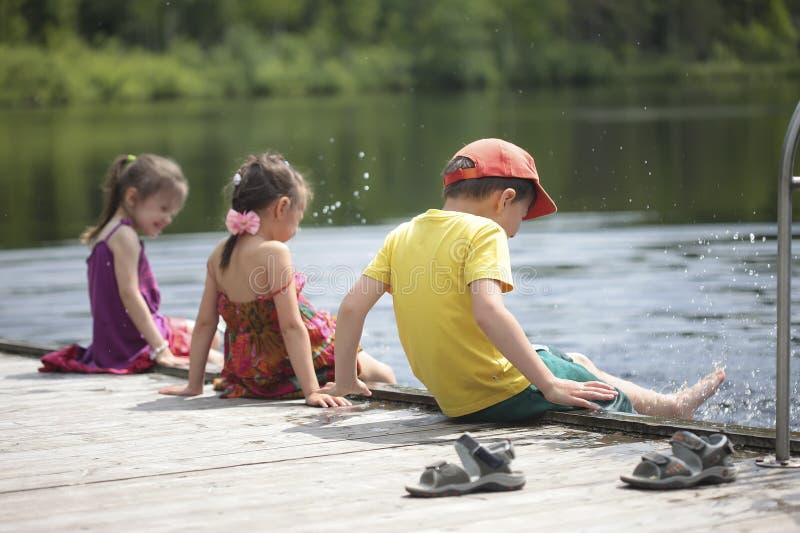 Drie vrolijke jonge geitjes die op het meer spelen royalty-vrije stock fotografie