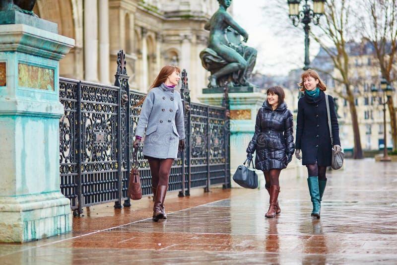 Drie vrolijke meisjes die samen in Parijs lopen royalty-vrije stock fotografie