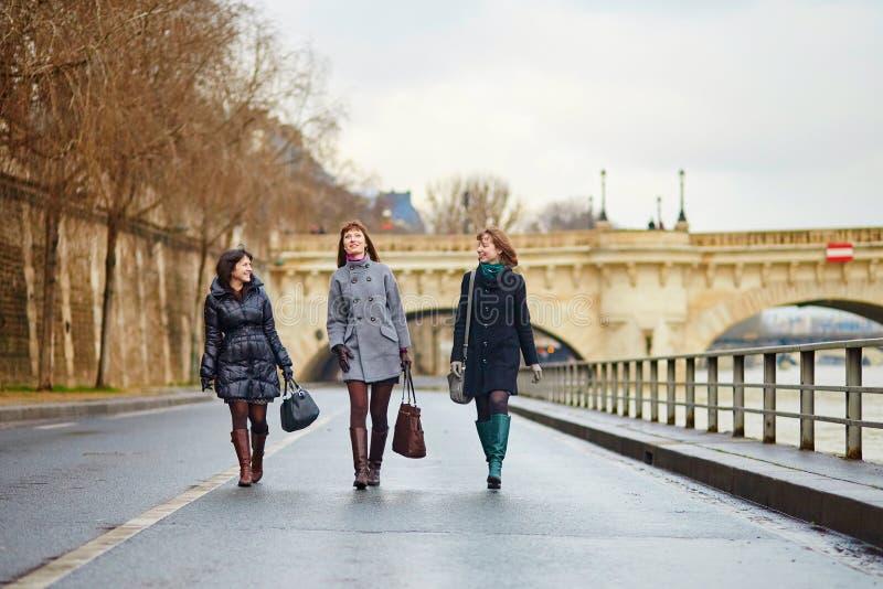 Drie vrolijke meisjes die samen in Parijs lopen royalty-vrije stock foto