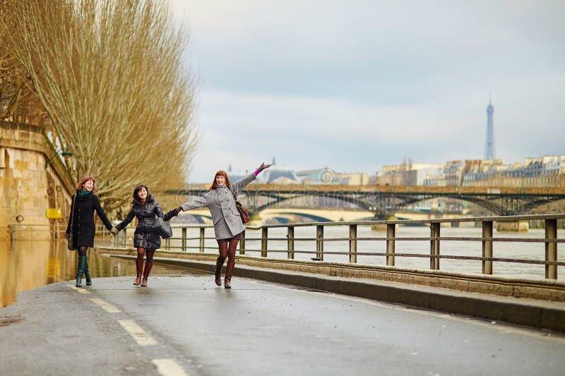 Drie vrolijke meisjes die samen in Parijs lopen stock foto's