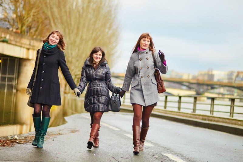 Drie vrolijke meisjes die samen in Parijs lopen royalty-vrije stock afbeeldingen