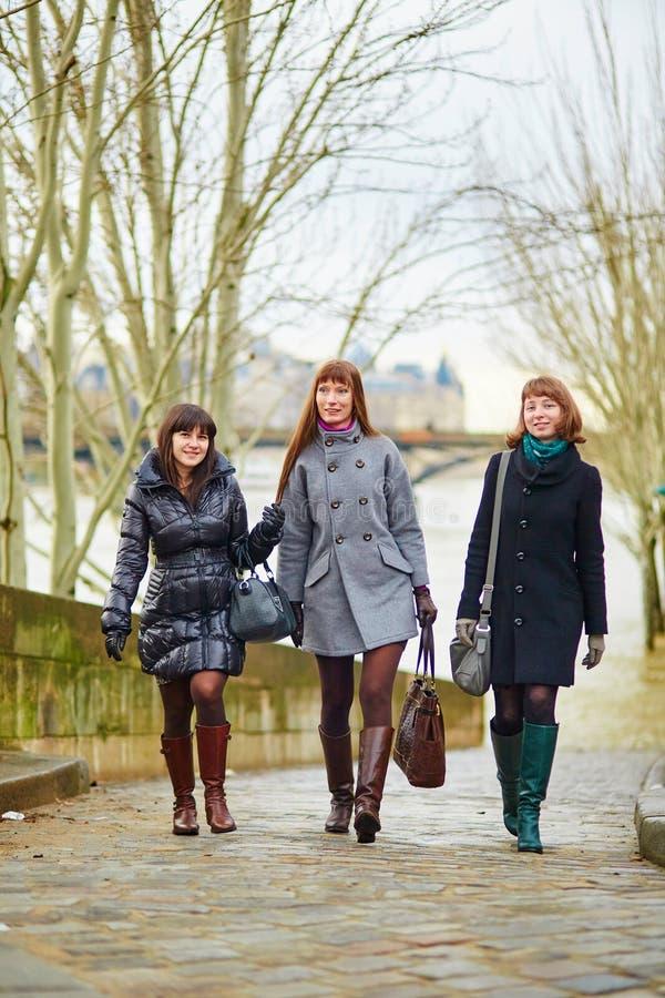 Drie vrolijke meisjes die samen in Parijs lopen royalty-vrije stock foto's