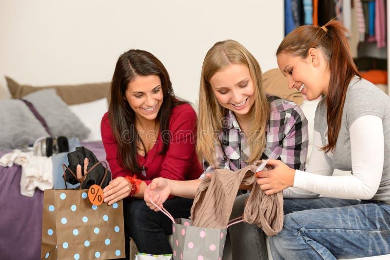 Drie vrolijke meisjes met kleren van verkoop royalty-vrije stock foto