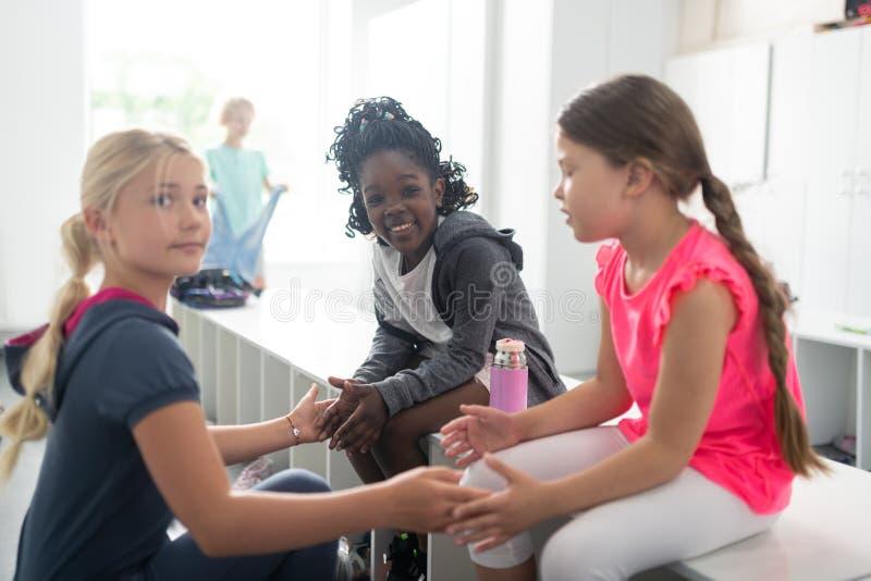 Drie vrolijke schoolmeisjes die na klassen op elkaar inwerken royalty-vrije stock fotografie