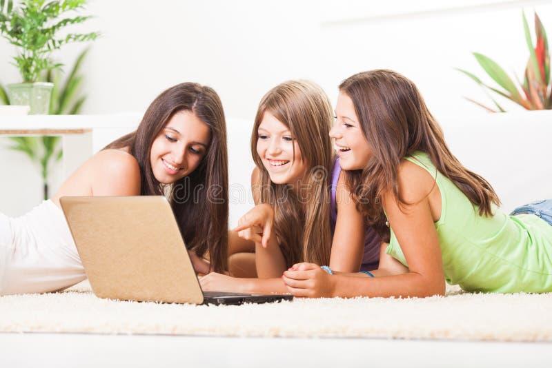 Drie vrolijke Vrienden met laptop royalty-vrije stock fotografie