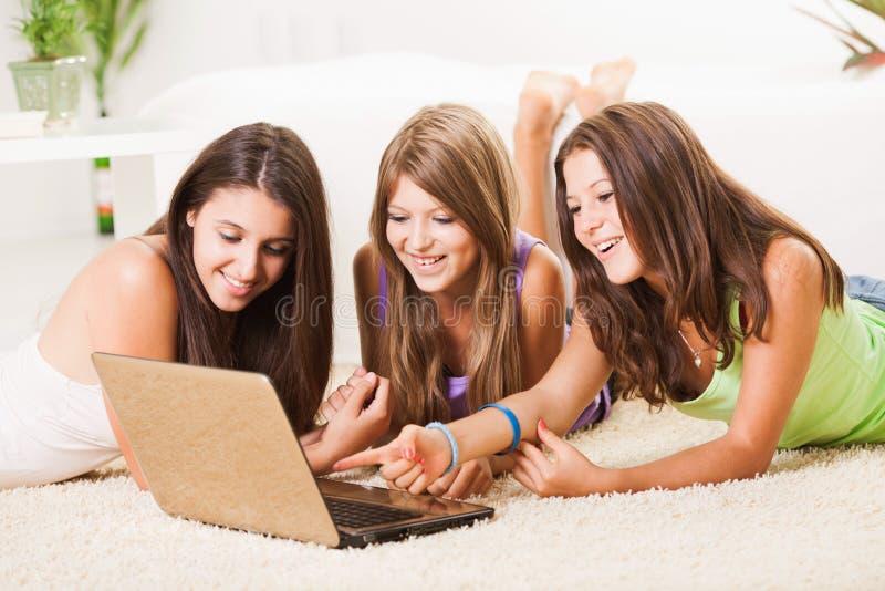 Drie vrolijke Vrienden met laptop stock afbeelding