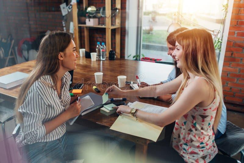 Drie vrolijke vrouwelijke middelbare schoolstudenten die voor examen in een schoolbibliotheek voorbereidingen treffen royalty-vrije stock afbeeldingen