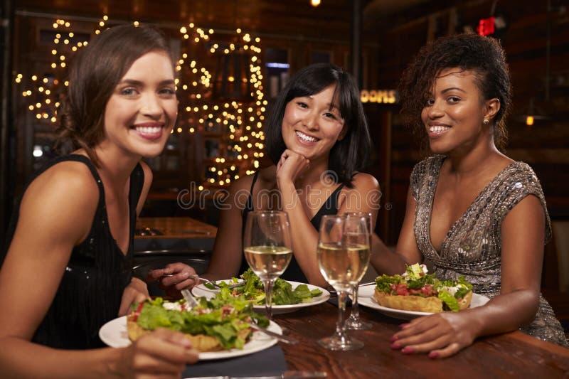 Drie vrouwelijke vrienden bij diner in restaurant kijken aan camera royalty-vrije stock foto's