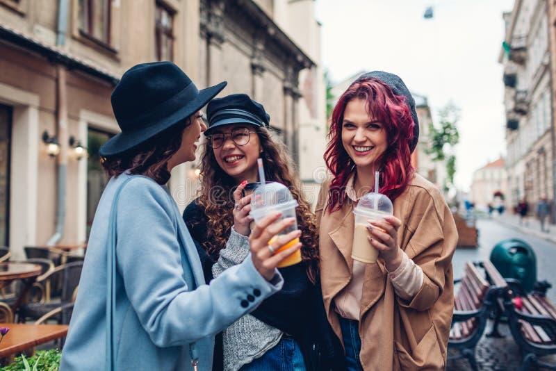 Drie vrouwelijke vrienden die dranken hebben in openlucht Vrouwen die koffie, jus d'orange en theekoppen clinking royalty-vrije stock foto