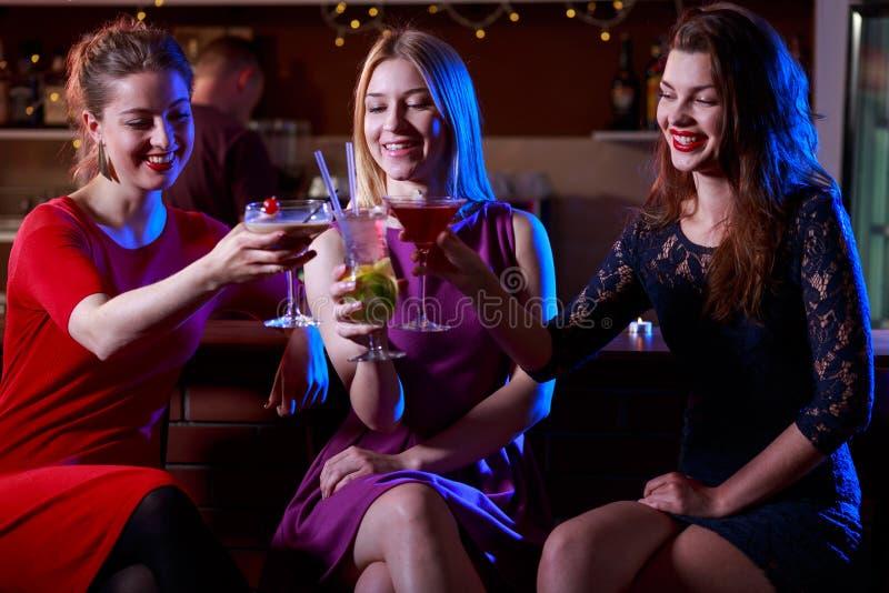 Drie vrouwelijke vrienden die van het drinken genieten royalty-vrije stock afbeeldingen