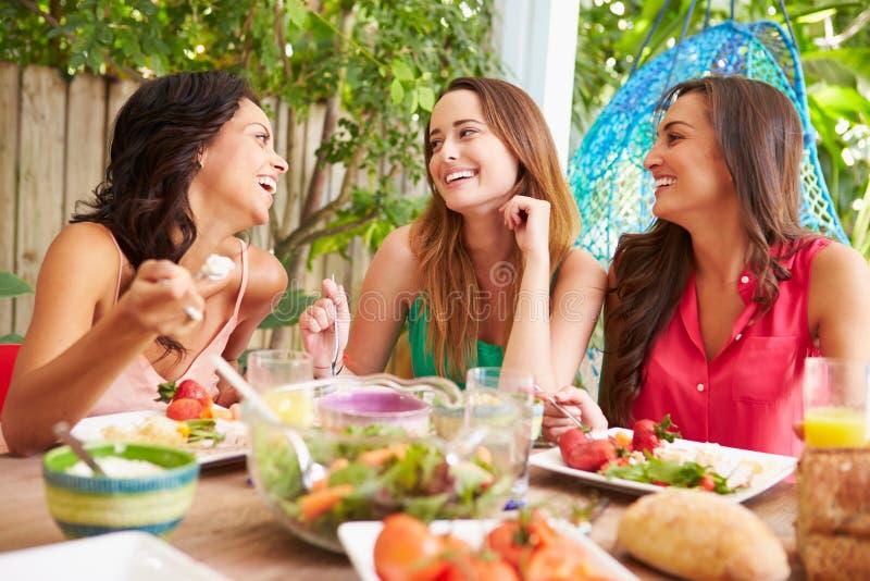 Drie Vrouwelijke Vrienden die van Maaltijd in openlucht thuis genieten stock foto