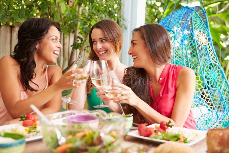 Drie Vrouwelijke Vrienden die van Maaltijd in openlucht thuis genieten stock afbeeldingen