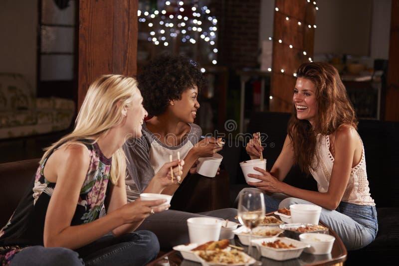 Drie vrouwelijke vrienden hangen uit het eten van een Chinees meeneem stock fotografie