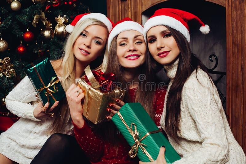 Drie vrouwelijke vrienden in santahoeden het houden stelt voor royalty-vrije stock foto's