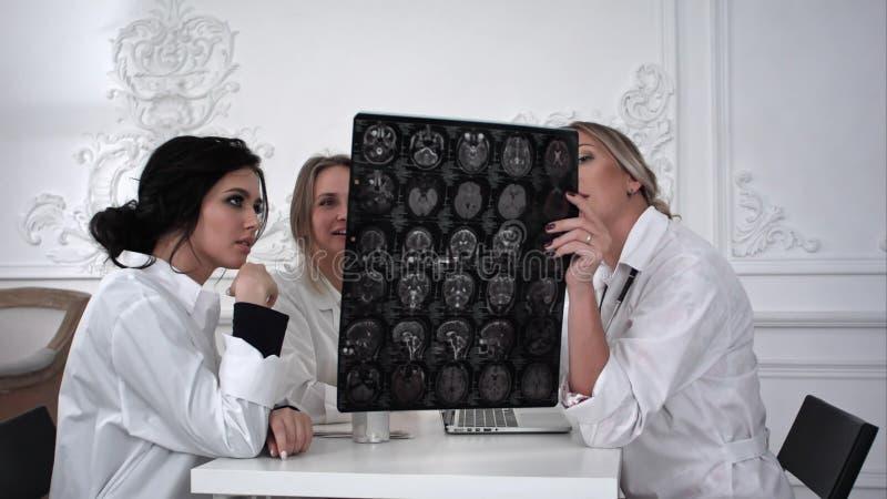 Drie vrouwen artsen die met x-ray foto in het bureau werken royalty-vrije stock afbeelding