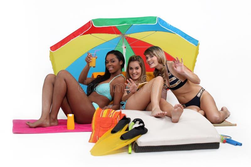 Drie vrouwen die bij het strand hebben stock afbeelding