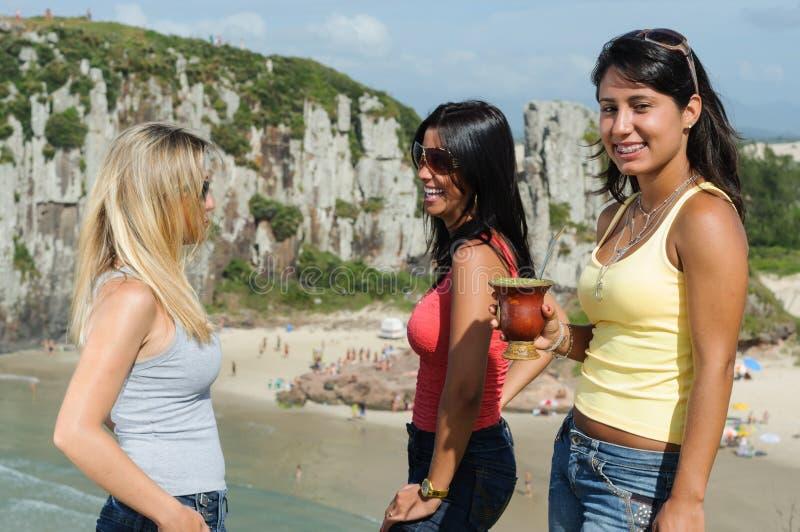 Drie vrouwen die chimarrão op Torres-strand nemen royalty-vrije stock afbeeldingen