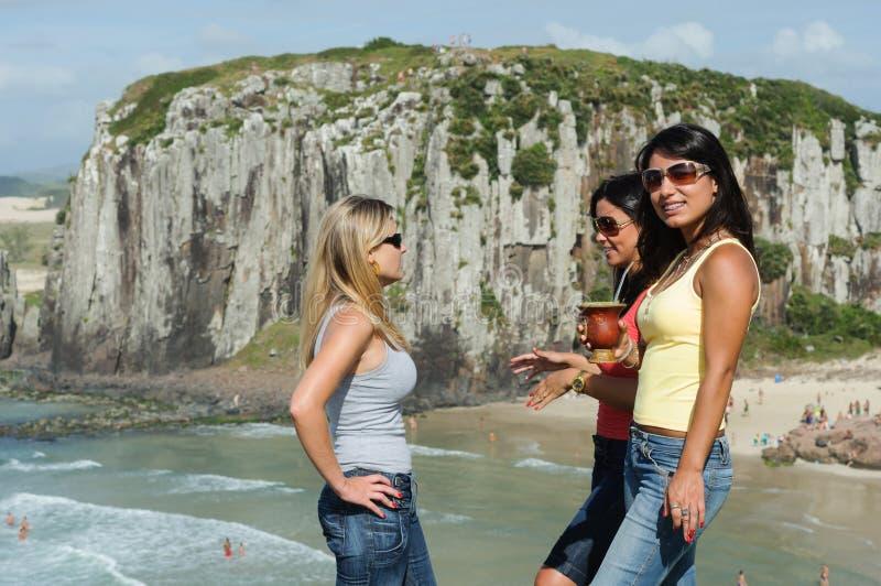 Drie vrouwen die chimarrão op Torres-strand nemen royalty-vrije stock fotografie