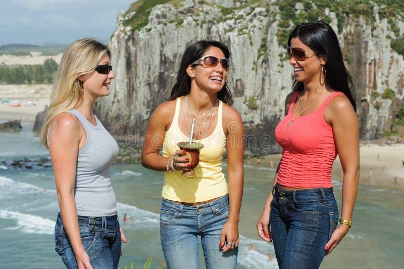 Drie vrouwen die chimarrão op Torres-strand nemen stock fotografie