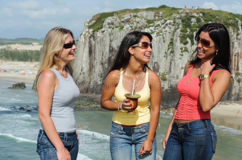 Drie vrouwen die chimarrão op Torres-strand nemen stock foto's