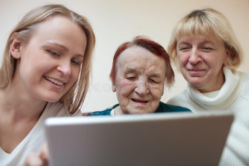 Drie vrouwen die een slimme tablet gebruiken stock foto
