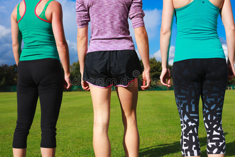 Drie vrouwen die sportkleding in het park dragen stock foto