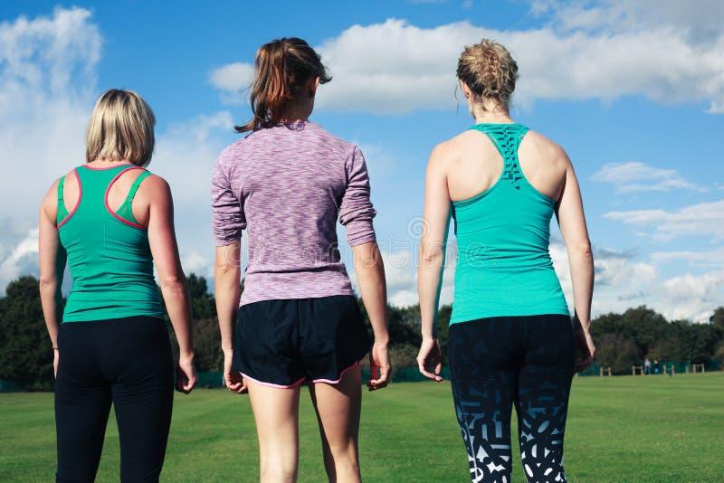 Drie vrouwen die sportkleding in het park dragen royalty-vrije stock fotografie