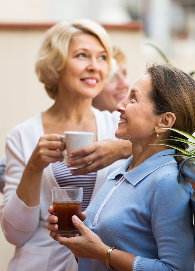 Drie vrouwen die thee drinken bij balkon stock afbeelding