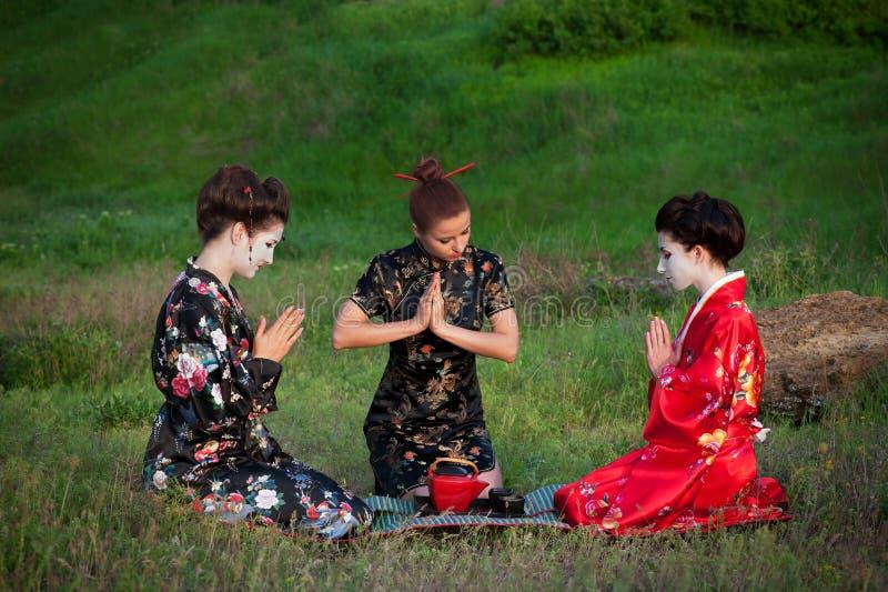 Drie vrouwen die thee op een Aziatische manier drinken royalty-vrije stock foto's