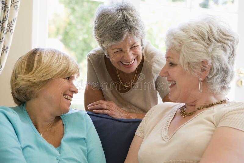Drie vrouwen in en woonkamer die spreekt glimlacht royalty-vrije stock foto