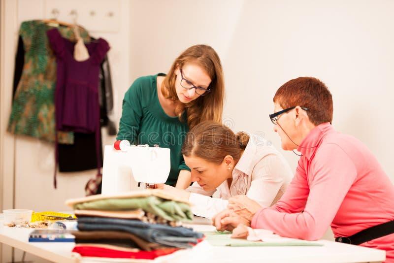 Drie vrouwen naaien op handcraftworkshop Zij onderwijzen royalty-vrije stock foto