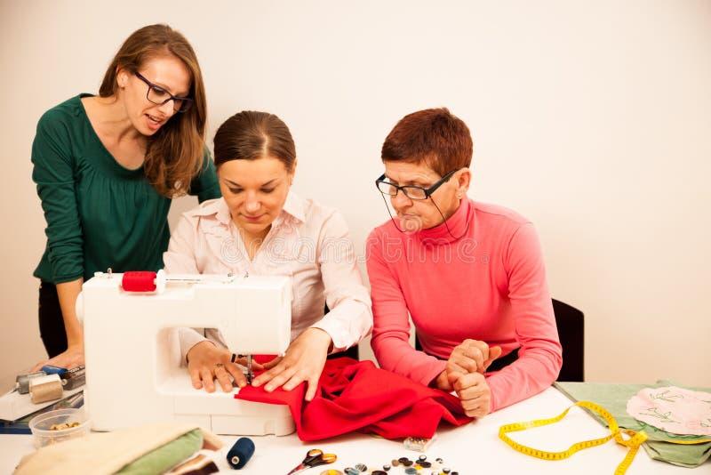 Drie vrouwen naaien op handcraftworkshop Zij onderwijzen royalty-vrije stock afbeelding