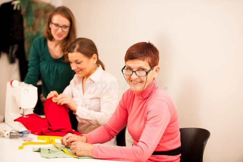 Drie vrouwen naaien op handcraftworkshop Zij onderwijzen stock foto's