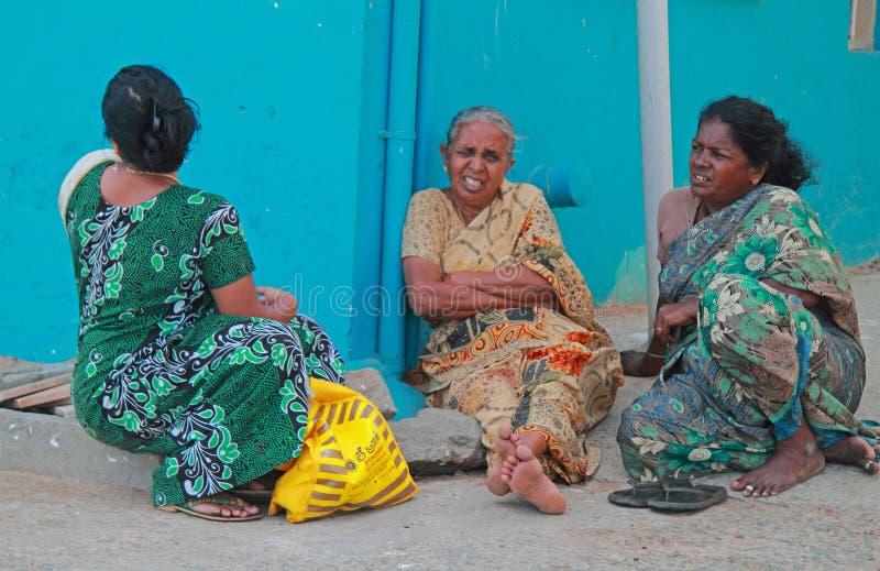 Drie vrouwen zitten openlucht in Kanyakumari, India stock foto
