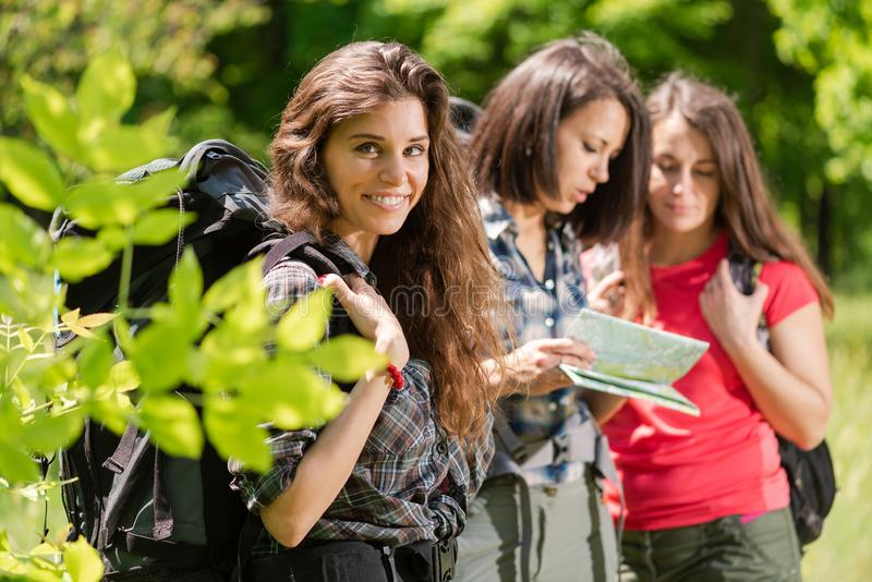 Drie vrouwentoeristen met rugzakken in bos stock afbeelding