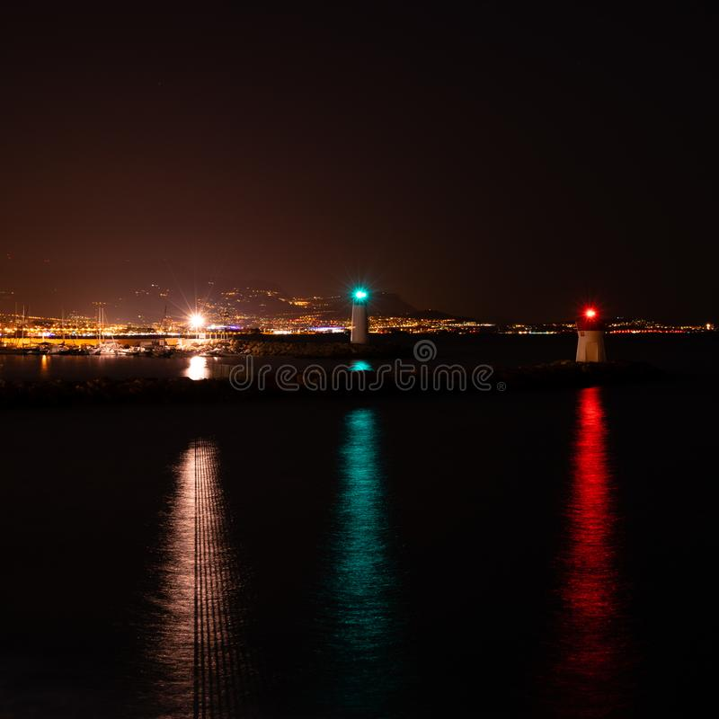 Drie vuurtorens met kleurrijke lichten in de Baai die de stad overzien bij nacht royalty-vrije stock foto