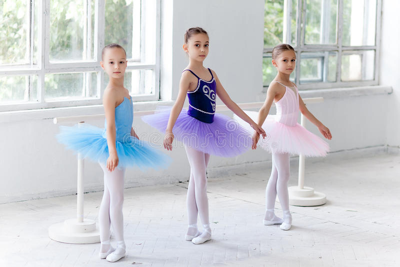 Drie weinig in tutu zitten en balletmeisjes die samen stellen royalty-vrije stock afbeeldingen