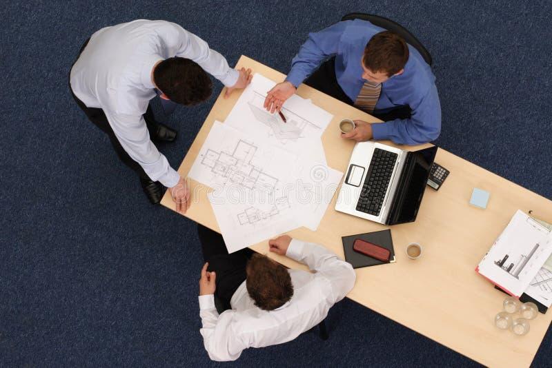 Drie werkende bedrijfsmensen over blauwdrukken stock fotografie