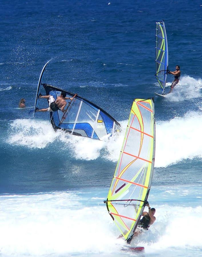 Drie windsurfers in de golven stock afbeeldingen