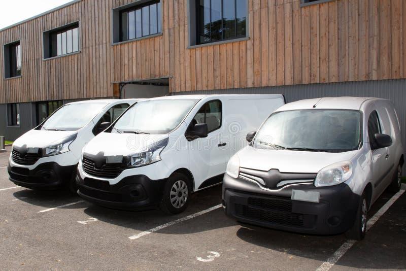 Drie Witte bestelwagens van Leveringsvrachtwagens die aan de Pakhuisbouw worden gesteund stock afbeeldingen